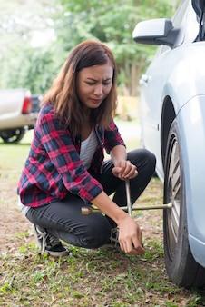 Junge hipster frau überprüfung eines flachen reifen auf ihr auto versuchen zu beheben.