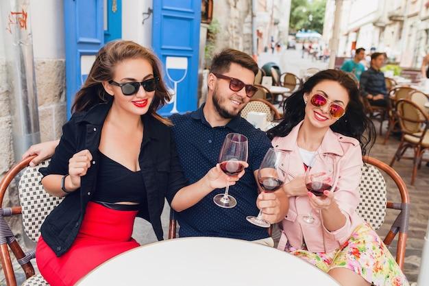 Junge hipster-gesellschaft von freunden, die am café sitzen