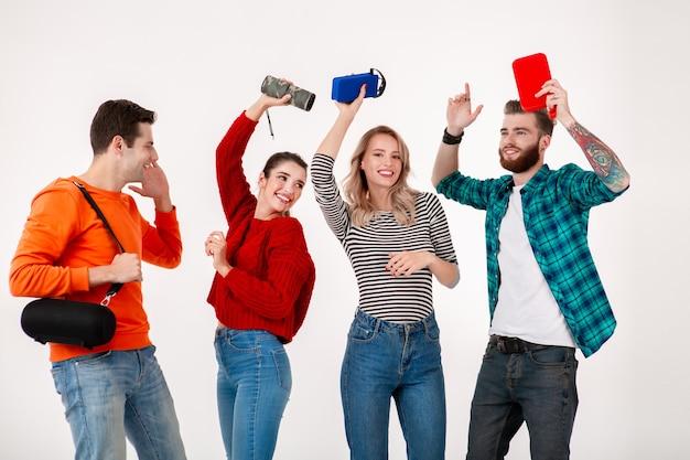 Junge hipster-gesellschaft von freunden, die spaß haben, zusammen lächelnd musik auf drahtlosen lautsprechern hörend, tanzend lachend isolierte weiße wand im bunten stilvollen outfit tanzen