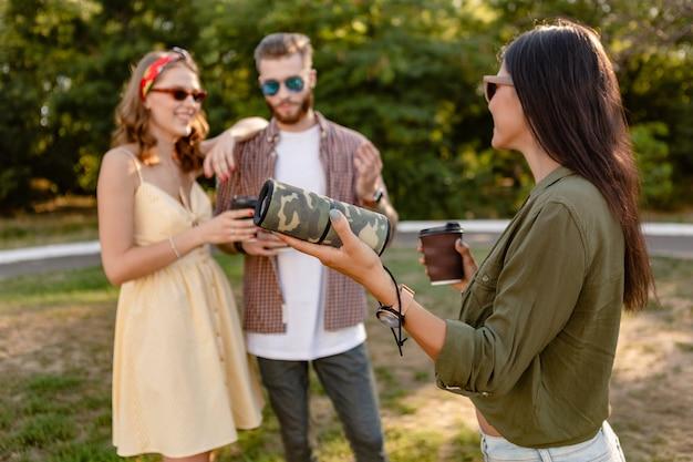 Junge hipster-gesellschaft von freunden, die spaß zusammen im park lächelnd musik auf drahtlosem lautsprecher hörend, sommersaison haben