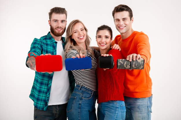 Junge hipster-gesellschaft von freunden, die spaß zusammen lächelnd beim hören von musik auf drahtlosen lautsprechern haben, isolierter weißer hintergrund des studios im bunten stilvollen outfit, geräte in der kamera zeigend