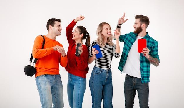 Junge hipster-gesellschaft von freunden, die zusammen spaß haben, lächeln, musik auf drahtlosen lautsprechern hören, lachend tanzen