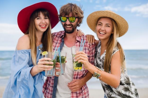 Junge hipster-gesellschaft von freunden im urlaub am strand, mojito-cocktail trinkend, glücklich positiv, sommerart, glücklich lächelnd, zwei frauen und mann, die spaß zusammen haben, reden, flirten, romantik, drei