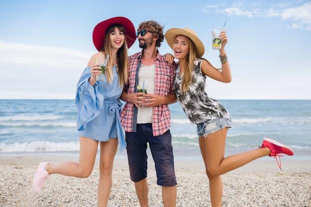Junge hipster-gesellschaft von freunden im urlaub am strand, mojito-cocktail trinkend