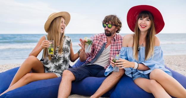 Junge hipster-gesellschaft von freunden im urlaub, die am strand auf sitzsäcken sitzen