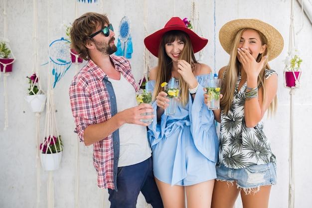 Junge hipster-gesellschaft von freunden im urlaub im sommercafé, mojito-cocktails trinkend, glücklicher positiver stil, glücklich lächelnd, zwei frauen und mann, die spaß zusammen haben, reden, flirten, romantik, drei