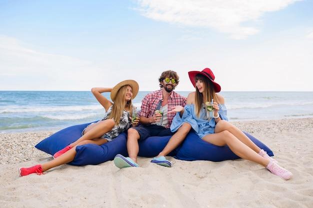 Junge hipster-gesellschaft von freunden in den sommerferien, die am strand auf sitzsäcken sitzen, spaß zusammen haben, mojito-cocktail trinken, glücklich, lächelnd, positive, lustige emotion, drei-personen-party