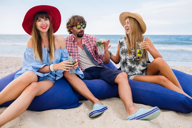 Junge hipster lächelnde gesellschaft von glücklichen freunden im urlaub, die in sitzsäcken auf einer strandparty sitzen und mojito-cocktail trinken