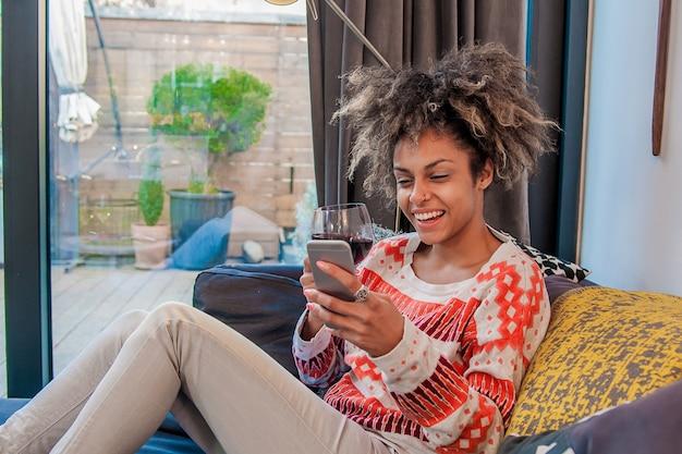 Junge hipster mädchen mit modernen smartphone-gerät beim sitzen zu hause und kommunizieren mit freunden in sozialen netzwerken, weibliche freiberufler arbeiten von zu hause aus, glück und genuss lebensstil