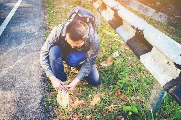 Junge hipster mann hände binden schnürsenkel auf der straße