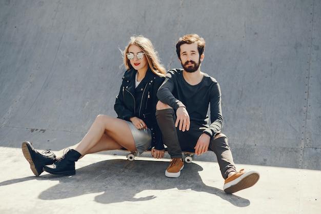 Junge hipster sitzen in einem sonnigen sommerpark mit einem skateboard in ihren händen