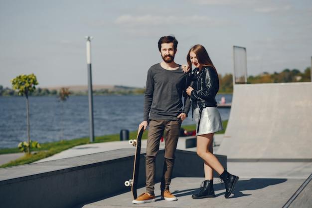 Junge hipster stehen in einem sonnigen sommerpark mit einem skateboard in ihren händen