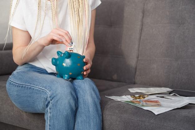 Junge hipsterfrau, die 10 euro in sparbüchse für reisen setzt, die auf sofa zu hause sitzen. einsparungskonzept