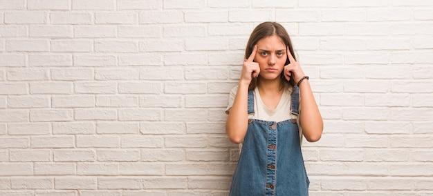 Junge hipsterfrau, die eine konzentrationsgeste tut