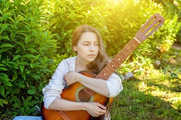 Junge hipsterfrau, die im gras sitzt und gitarre auf park oder garten spielt