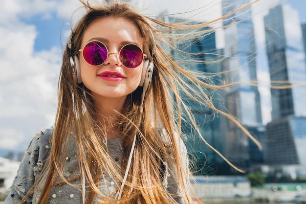 Junge hipsterfrau, die spaß in der straße hat, die musik auf kopfhörern hört, rosa sonnenbrille tragend