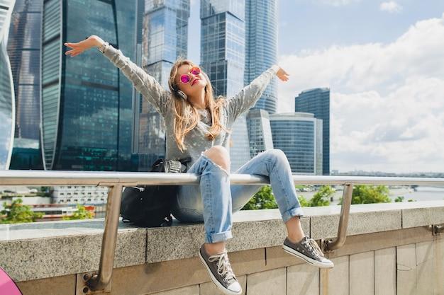 Junge hipsterfrau, die spaß in der straße hat, die musik auf kopfhörern hört
