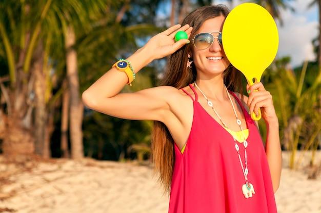 Junge hipsterfrau, die tischtennis am tropischen strand, sommerferien spielt.