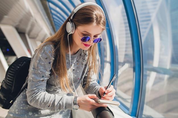 Junge hipsterfrau im lässigen outfit, das spaß hat, musik in den kopfhörern zu hören