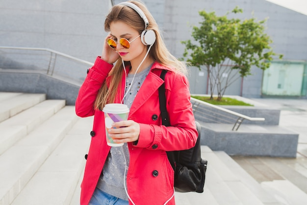 Junge hipsterfrau im rosa mantel, jeans in der straße mit rucksack und kaffee, die musik auf kopfhörern hören