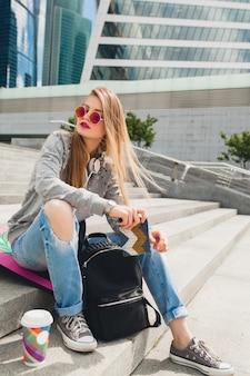 Junge hipsterfrau in der straße mit ausgleichsbrett, das pullover und jeans trägt