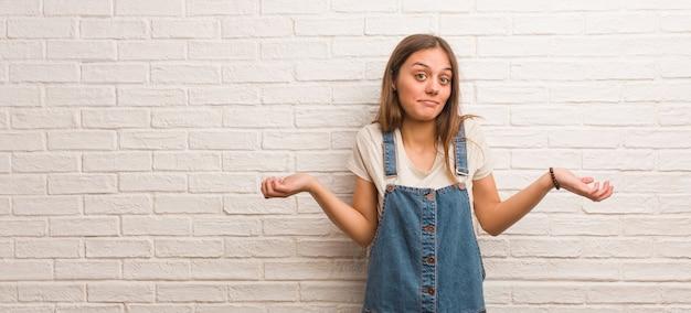 Junge hipsterfrau zweifelt und zuckt mit den schultern