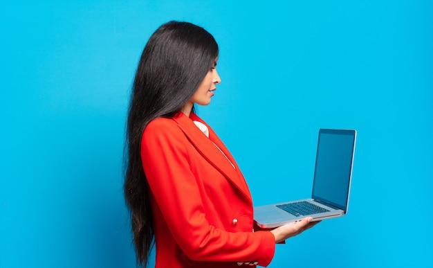 Junge hispanische frau auf der profilansicht, die den raum nach vorne kopieren möchte, denkt, sich vorstellt oder träumt. laptop-konzept