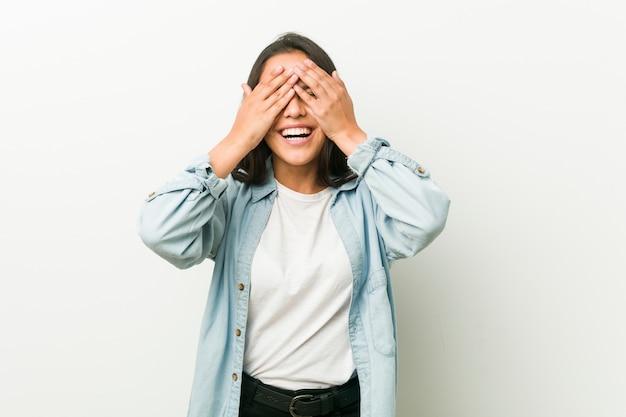 Junge hispanische frau deckt die augen mit den händen, lächelt breit und wartet auf eine überraschung.