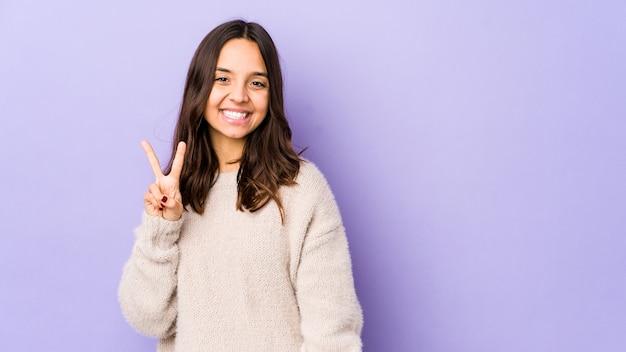 Junge hispanische frau der gemischten rasse isolierte freudig und sorglos, ein friedenssymbol mit den fingern zeigend.