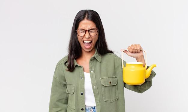 Junge hispanische frau, die aggressiv schreit, sehr wütend aussieht und eine teekanne hält