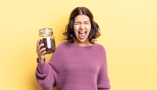 Junge hispanische frau, die aggressiv schreit und sehr wütend aussieht. kaffeebohnen-konzept
