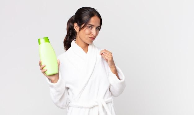 Junge hispanische frau, die arrogant, erfolgreich, positiv und stolz aussieht, bademantel trägt und ein shampoo hält