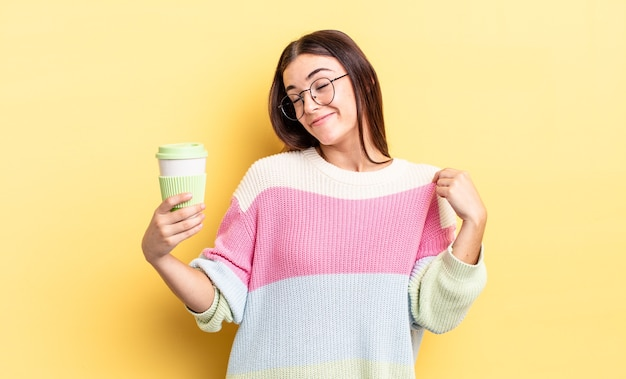 Junge hispanische frau, die arrogant, erfolgreich, positiv und stolz aussieht. kaffee zum mitnehmen konzept