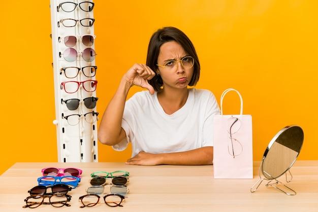 Junge hispanische frau, die auf brille versucht, isoliert zeigt eine abneigungsgeste, daumen nach unten. uneinigkeit konzept.