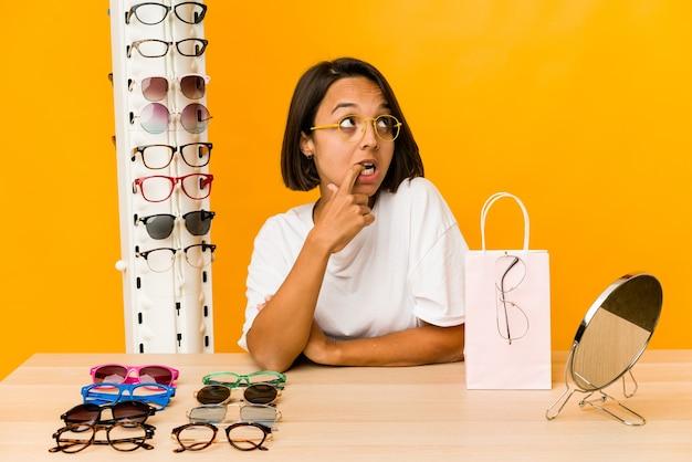Junge hispanische frau, die auf brille versucht, isolierte entspanntes denken über etwas, das einen kopienraum betrachtet.