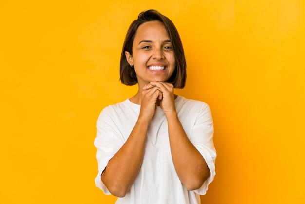 Junge hispanische frau, die auf gelb isoliert ist, hält hände unter kinn, schaut glücklich beiseite.