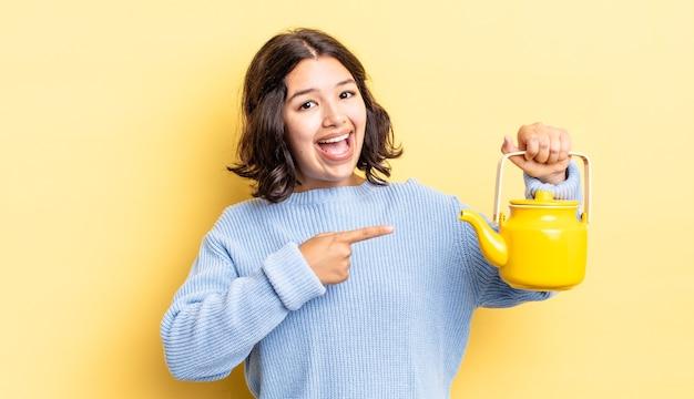 Junge hispanische frau, die aufgeregt und überrascht aussieht und auf die seite zeigt. teekannenkonzept