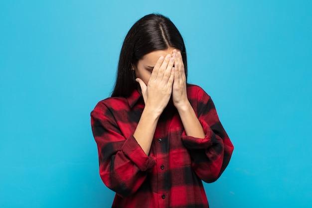 Junge hispanische frau, die augen mit händen mit einem traurigen, frustrierten ausdruck der verzweiflung, des weinens, der seitenansicht bedeckt