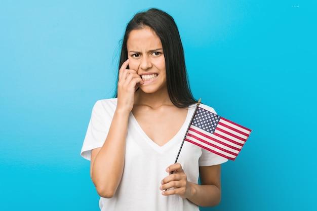 Junge hispanische frau, die beißende fingernägel einer flagge vereinigter staaten, nervös und sehr besorgt hält.
