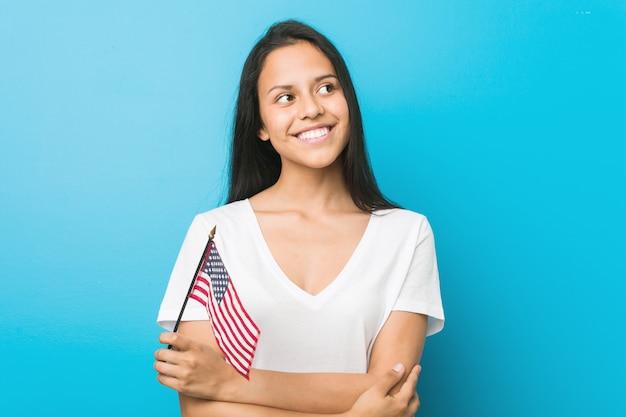 Junge hispanische frau, die das lächeln einer flagge vereinigter staaten überzeugt mit den gekreuzten armen hält.