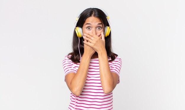 Junge hispanische frau, die den mund mit den händen bedeckt, mit einer schockierten musik mit kopfhörern
