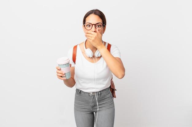 Junge hispanische frau, die den mund mit den händen mit einem schockierten bedeckt. studentisches konzept
