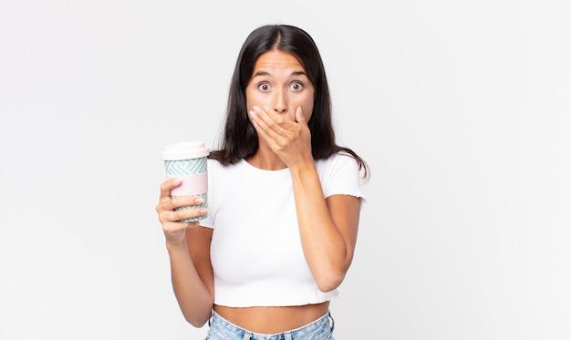 Junge hispanische frau, die den mund mit den händen mit einem schockierten bedeckt und einen kaffeebehälter zum mitnehmen hält