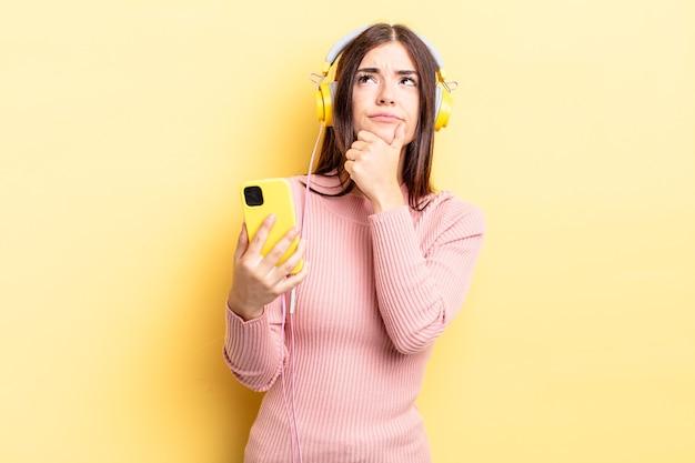 Junge hispanische frau, die denkt, sich zweifelnd und verwirrt fühlt. kopfhörer- und telefonkonzept