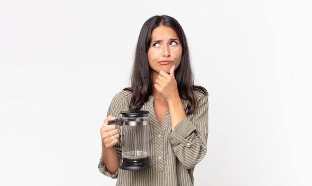 Junge hispanische frau, die denkt, sich zweifelnd und verwirrt fühlt und eine manuelle kaffeemaschine hält