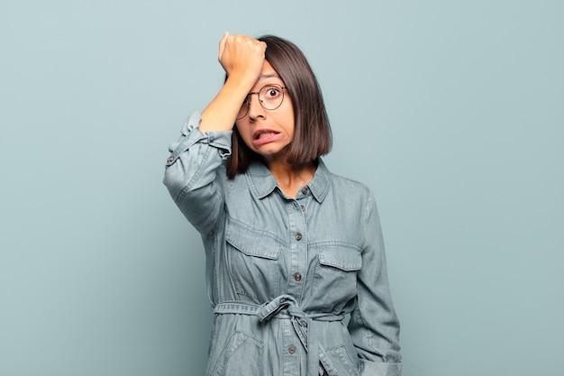Junge hispanische frau, die die handfläche zur stirn hebt und denkt, oops, nachdem sie einen dummen fehler gemacht oder sich daran erinnert hat, sich dumm zu fühlen