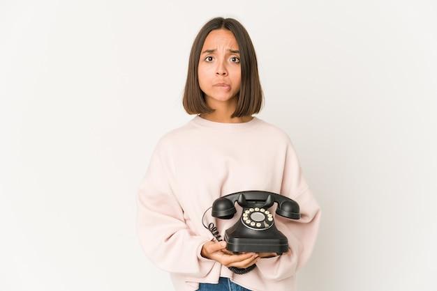 Junge hispanische frau, die ein altes telefon isoliert hält, verwirrt, fühlt sich zweifelhaft und unsicher.