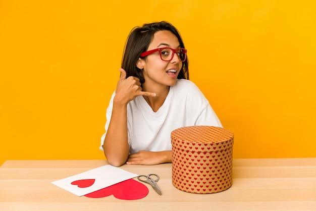 Junge hispanische frau, die ein isoliertes valentinsgeschenk vorbereitet, das eine handy-anrufgeste mit den fingern zeigt.