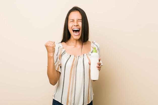 Junge hispanische frau, die ein sahneflaschenzujubeln sorglos und aufgeregt hält. sieg-konzept.