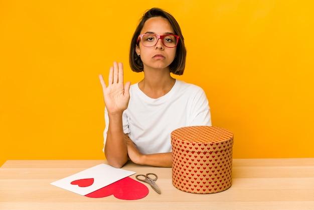 Junge hispanische frau, die ein valentinsgeschenk vorbereitet, das lokalisiert mit ausgestreckter hand steht, die stoppschild zeigt, das sie verhindert.